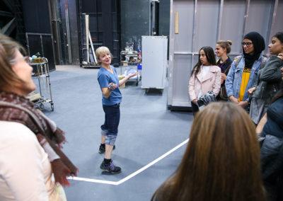 """Bei der Führung durch das Opernhaus kamen die Mädchen und jungen Frauen an verschiedene Abteilungen vorbei, in denen geplant, handwerklich gearbeitet oder Ausstattungsteile gelagert werden. Der Höhepunkt der Führung war der Gang auf die Bühne, wo fleißig das Bühnenbild für die abendliche Inszenierung bereitgestellt wurde. Hier zeigt eine Mitarbeiterin der Oper Frankfurt den Workshop-Teilnehmerinnen eine Requisite, die vor dem Auftritt nochmals getestet wird – eine Schreckschusswaffe, die für die erste Szene in """"Die Zauberflöte"""" beim Kampf mit der Schlange zu Gebrauch kommt.  © Wolfgang Runkel"""
