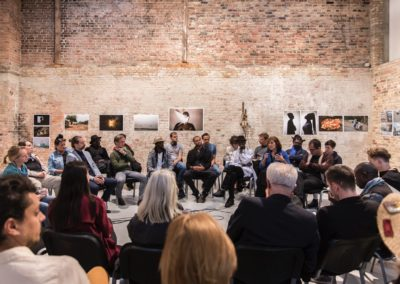 """Eröffnungsgespräch mit allen an der Ausstellung beteiligten Künstlerinnen und Künstlern im Freiraum in der Box, Berlin. Hintergrund: Mohamed Keita, """"Il Mondo é pianeta unico"""", Senegal, 2018 © Victoria Tomaschko"""